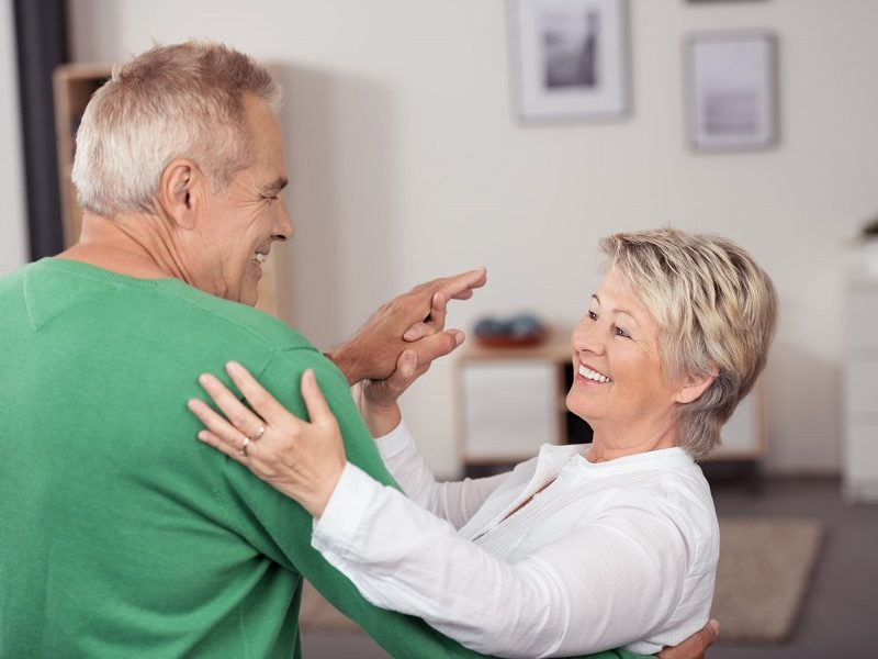 Active Middle Aged Couple Dancing So Sweet While Smiling Each Other at the Living Room Inside their House