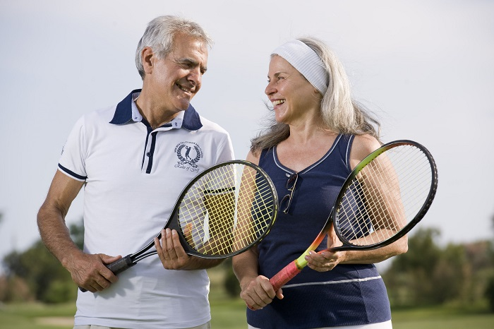 happy senior couple playing tennis