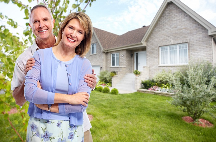 Happy elderly couple in love near new house. retirement concept.
