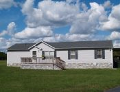 6448195 - gray trailer home with stone foundation or skirting and shutters in front of a beautiful sky.