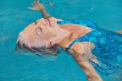 33758572 - happy senior woman relaxing in swimming pool with water yoga