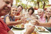 group of senior friends enjoying meal in outdoor restaurant